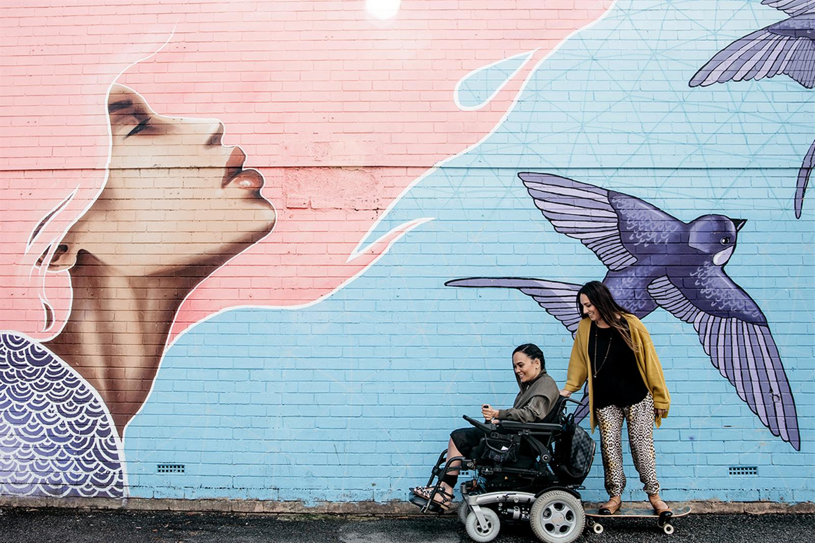 woman on skateboard follows a woman in wheelchair along street in front of bright blue and pink streetart
