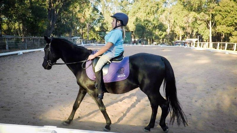 Profile shot of Bec riding her black pony in an outdoor arena.