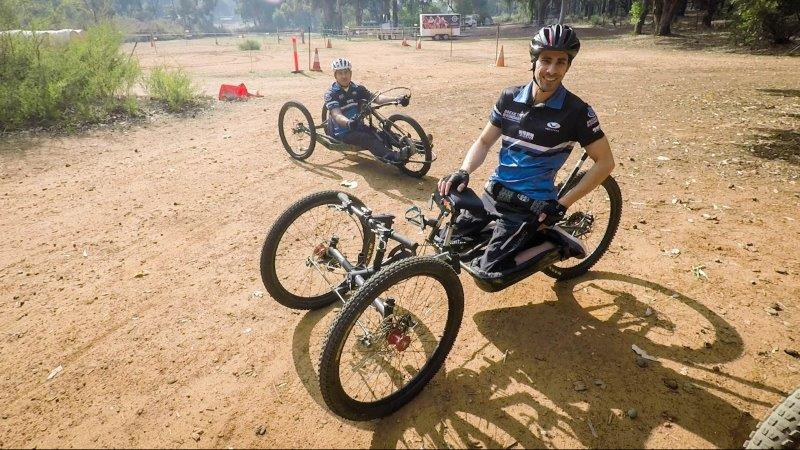 Two men sitting and kneeling on their off-road hand cycles on dirt, smiling.
