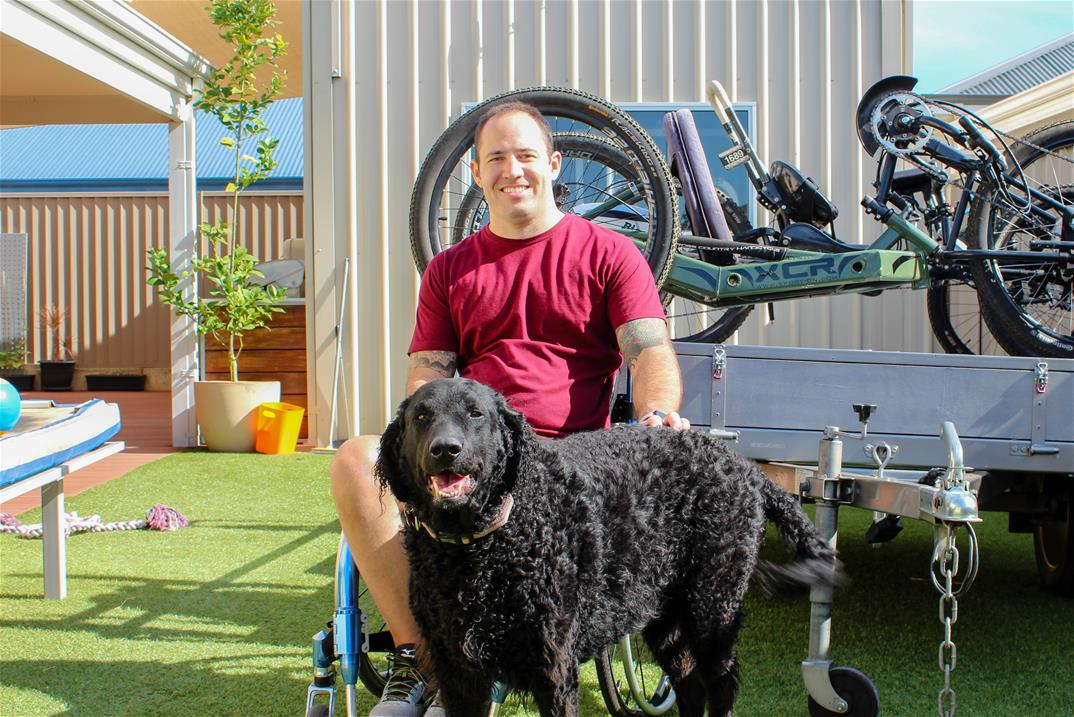 smiling man wearing red tshirt sits in a wheelchair patting a black dog in backyard