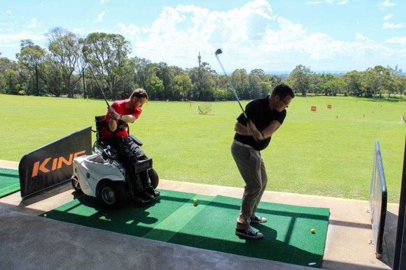 Two men at a driving range are in the motion of swinging their golf clubs. The man on the left wearing a red T-shirt is using a Paragolfer.