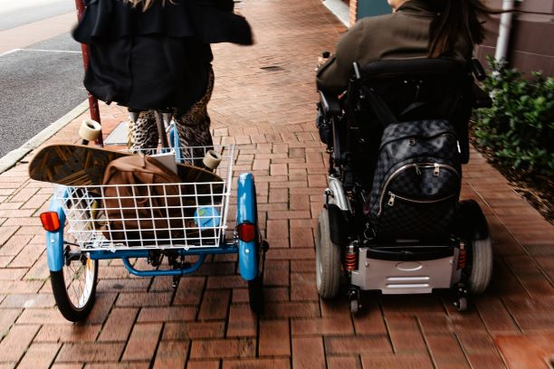 A woman in a wheelchair and a woman on a trike ride away