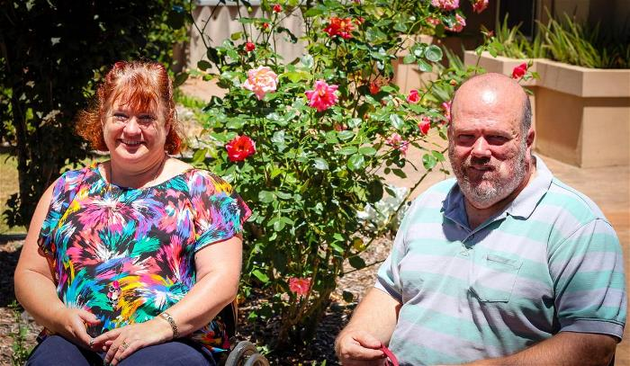 woman in floral top and man in striped polo sit in wheelchairs outside in garden