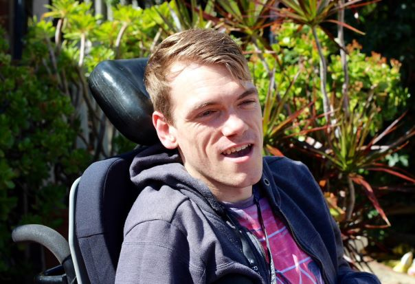 A young man in a wheelchair smiles to the right of the camera.
