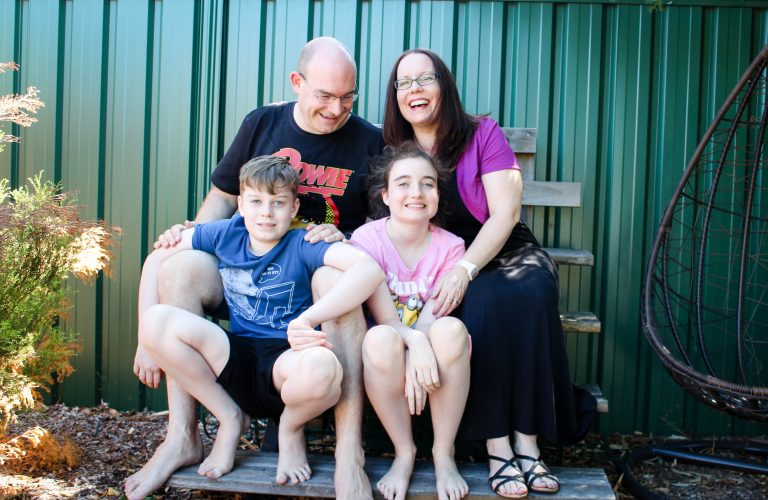 The Bolger family are seated together on a bench in their yard and smiling and laughing. Text overlay says blog post life as a family of four on the Autism spectrum