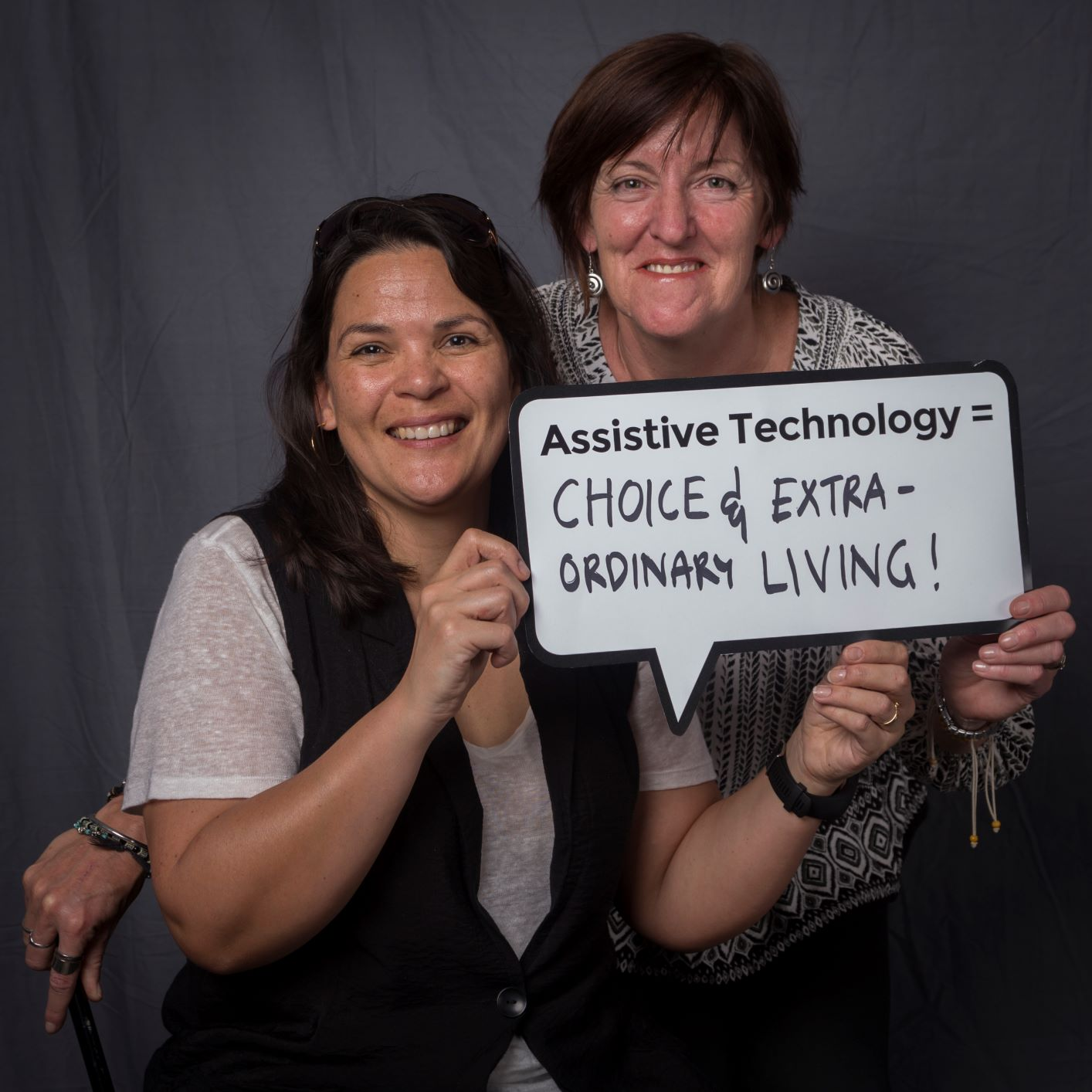 two woman holding up a speech bubble sign that reads assistive technology = choice and extra ordinary living