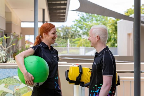 Two personal trainers hold exercise balls and smile at each other
