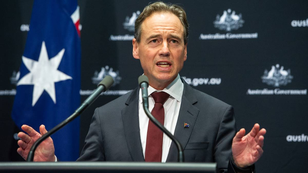 Picture of a man at a microphone with the Australian flag behind him