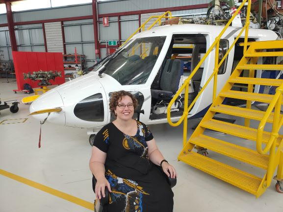 A lady sits in her wheelchair and smiles brightly. She is in an airplane hangar and a plane is behind her.