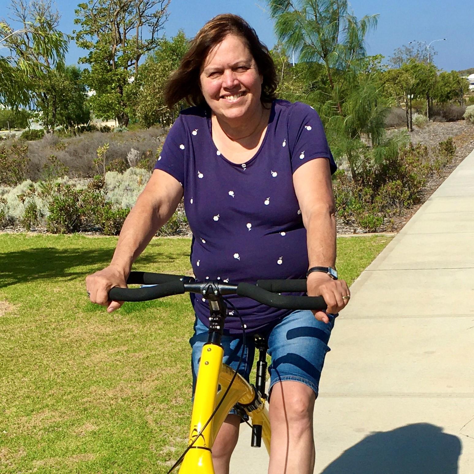 woman sits on yellow walking bike