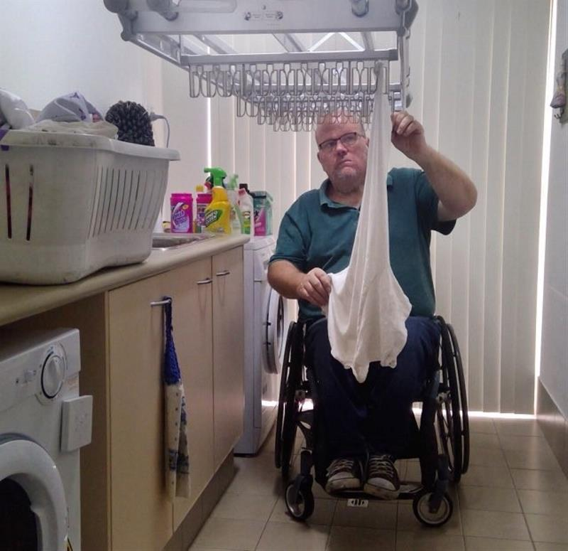 man using a wheelchair hangs up his laundry on mechanical clothes line
