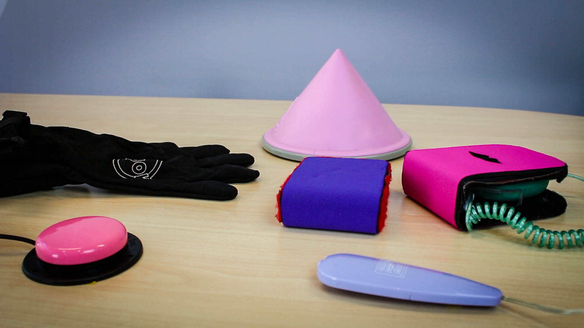brightly coloured sexual devices in different shapes displayed on table