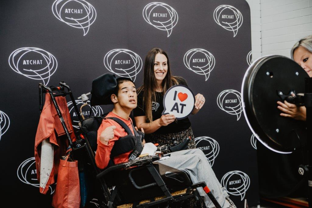 man using power wheelchair with woman and speech bubble sign